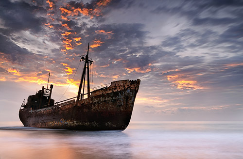 A shipwreck under the colorful sky of the golden hours