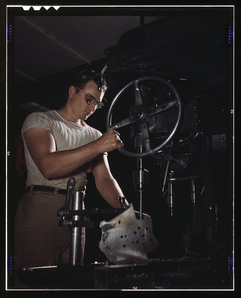 "An employee in the drill-press section of North American's huge machine shop runs mounting holes in a large dural casting, Inglewood, Calif. This plant produces the battle-tested B-25 (""Billy Mitchell"") bomber, used in General Doolittle's raid on Tokyo, and the P-51 (""Mustang"") fighter plane which was first brought into prominence by the British raid on Dieppe"