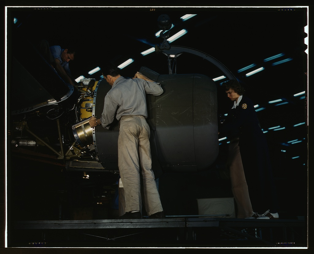 Lowering an engine in place in assembling a C-87 transport plane at the Consolidated Aircraft Corporation plant, Fort Worth, Texas