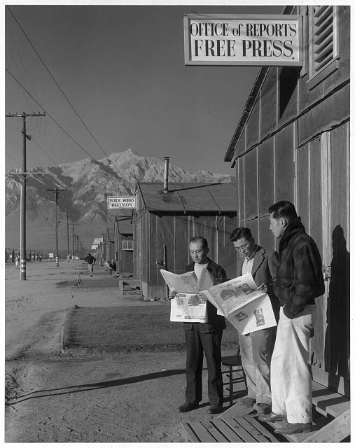 Roy Takeno, editor, and group reading paper in front of office ansel adams