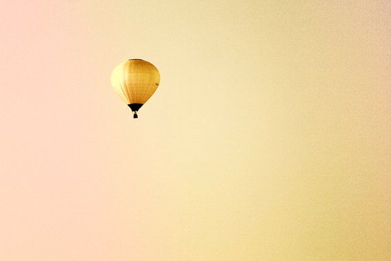 Yellow balloon floating on a yellow sky