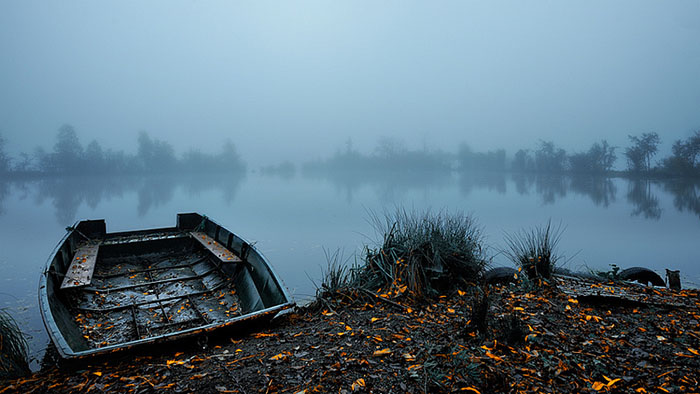 Rotting boat on water in autumn