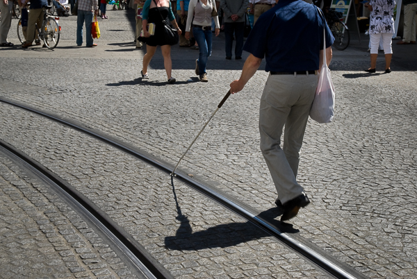 blind man with a walking stick on tram rail