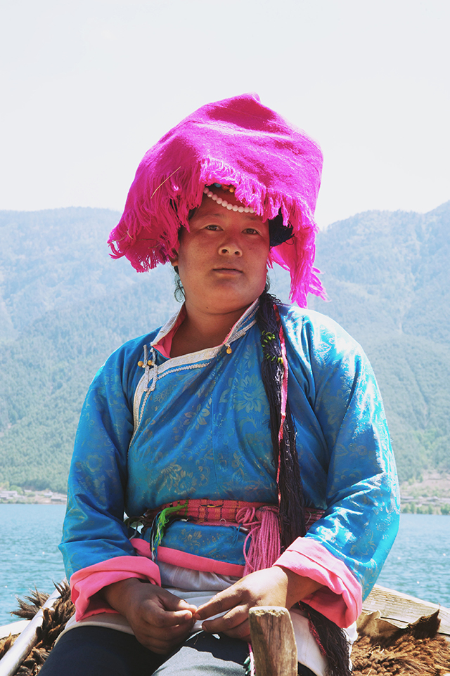 A Musuo woman sits at the end of the canoe