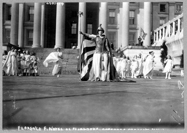 "German actress Hedwig Reicher wearing costume of ""Columbia"" with other suffrage pageant participants standing in background in front of the Treasury Building, March 3, 1913, Washington, D.C"