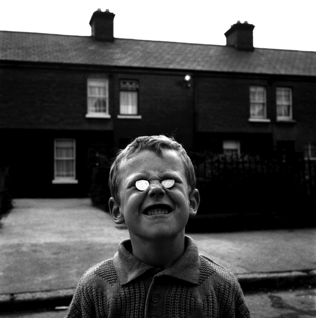 A boy poses with two coins in North Dublin's Linenhall Street, 1988